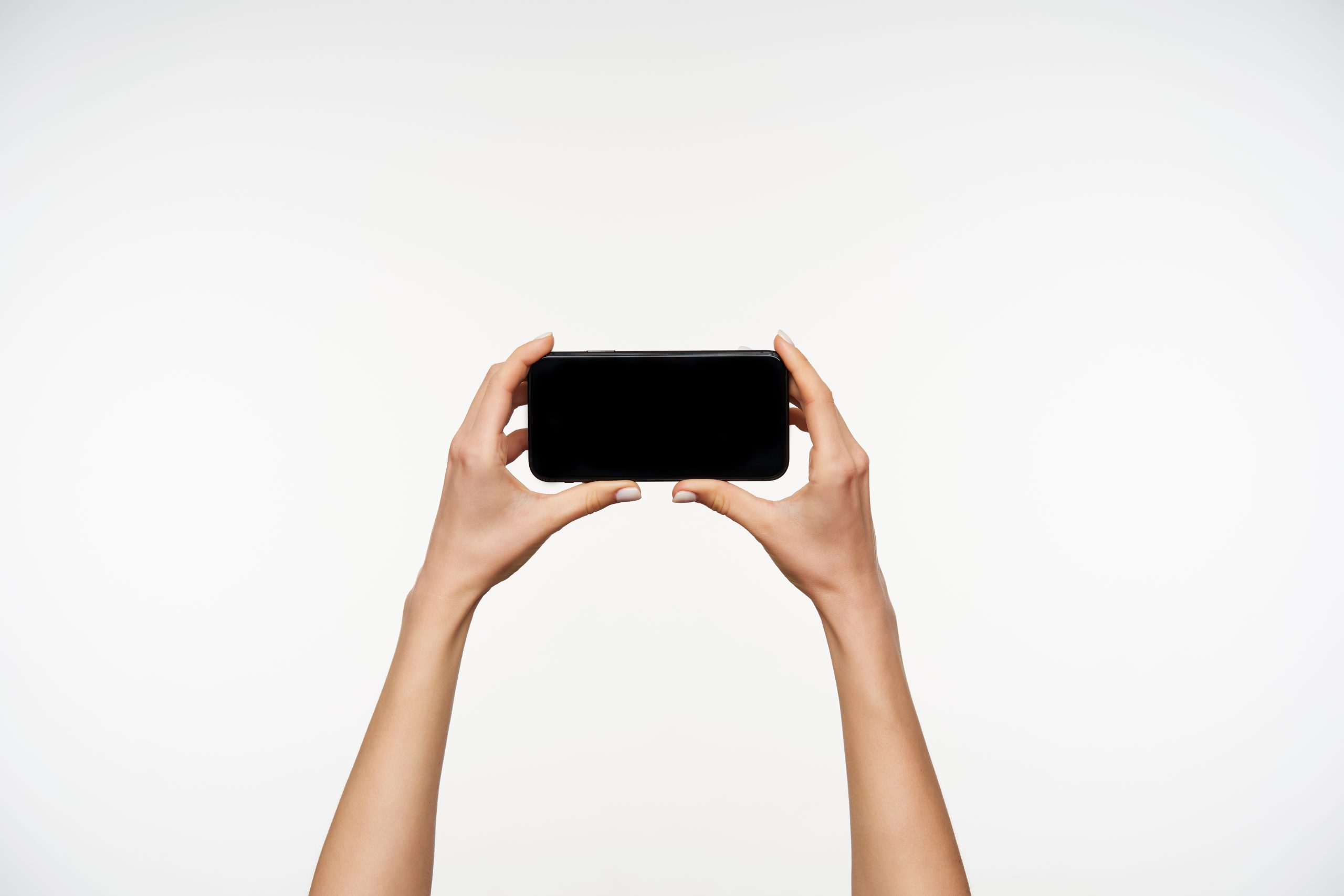 Cropped photo of raised fair-skinned woman's arms keeping mobile phone horizontally while going to watch video on it, standing over white background