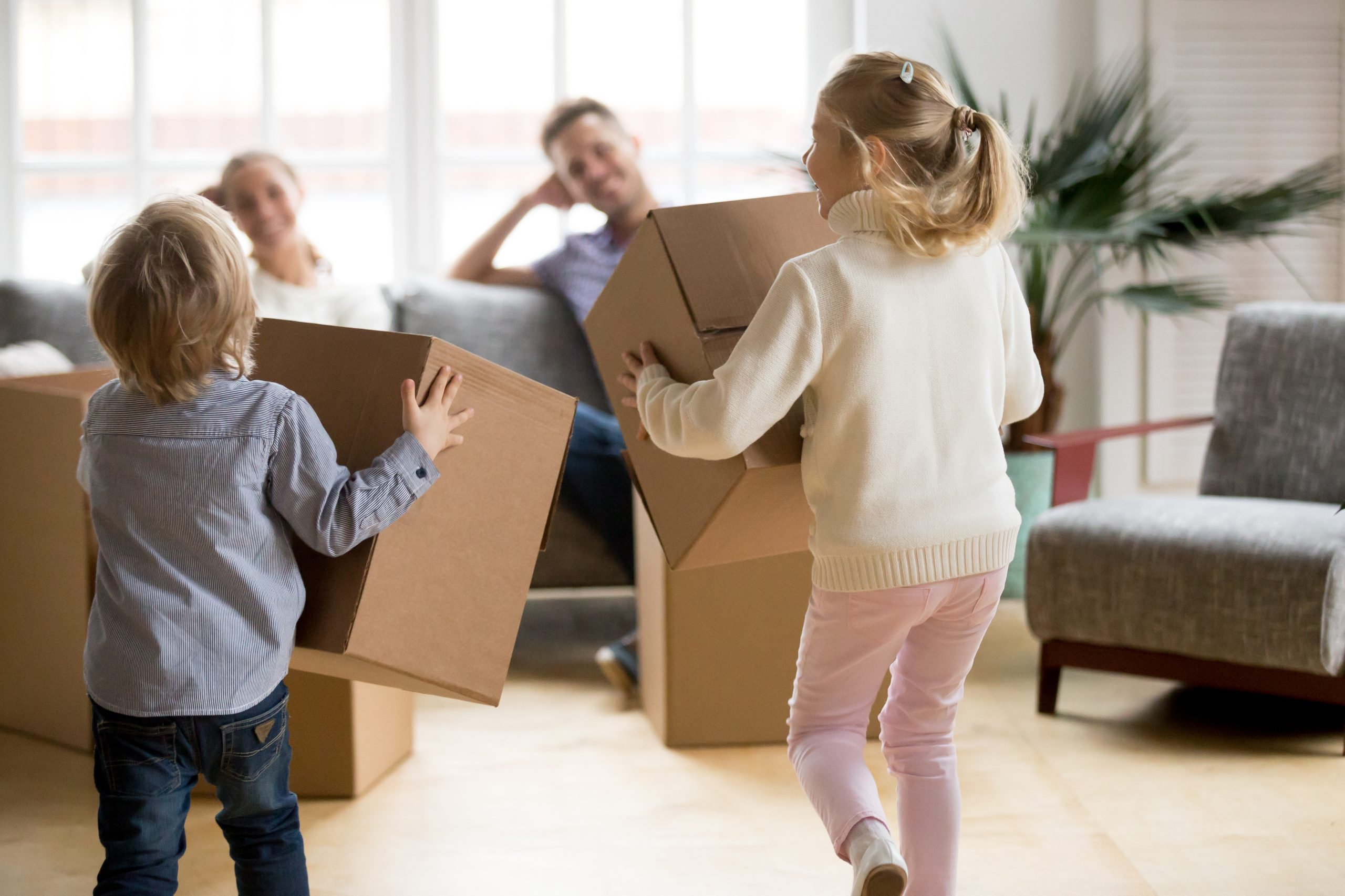 Rear view at kids playing with boxes on moving day, small brother and sister running holding belongings packing unpacking in new home, happy playful children having fun together enjoying relocation