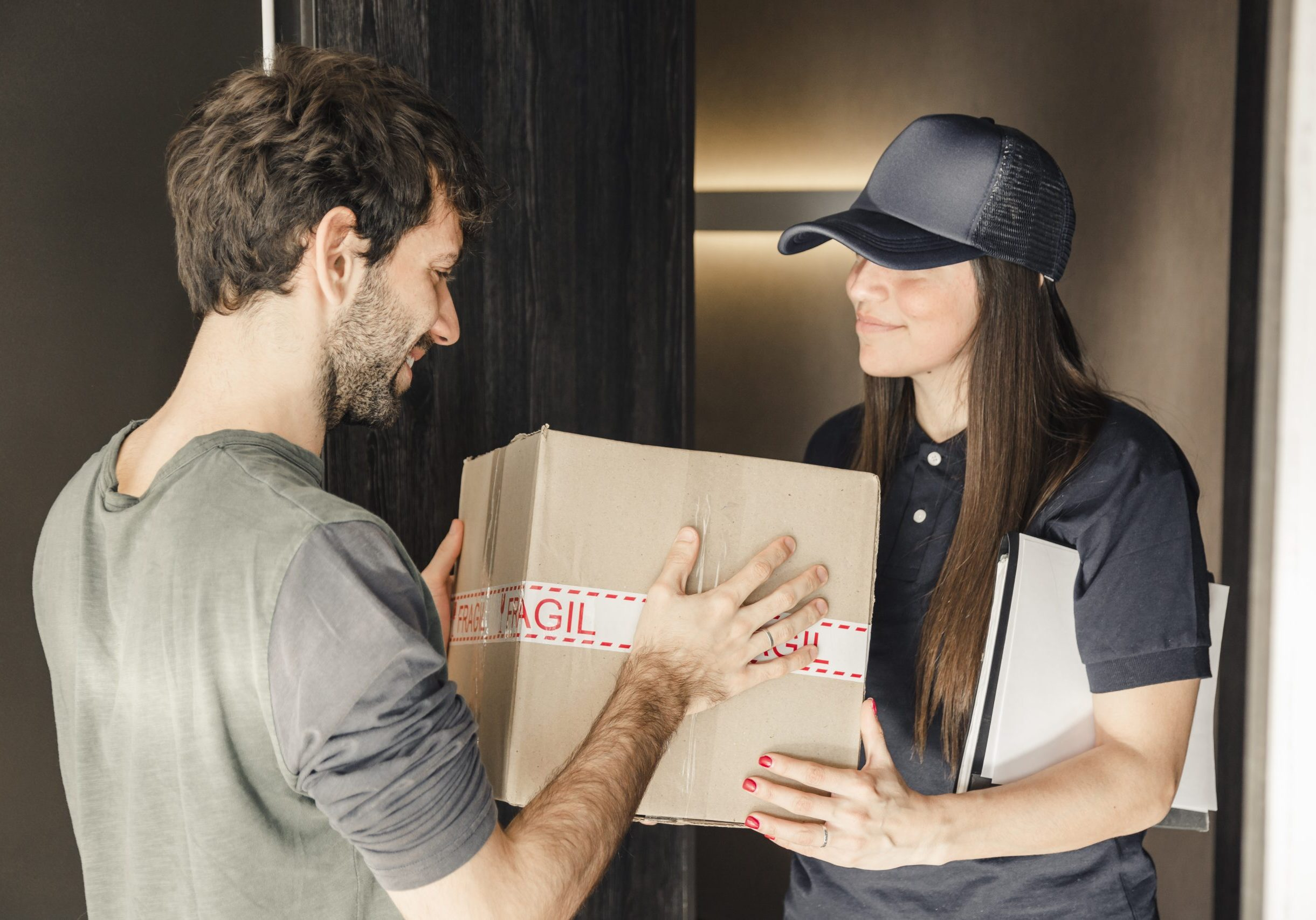 young-female-courier-delivering-parcel-man-home